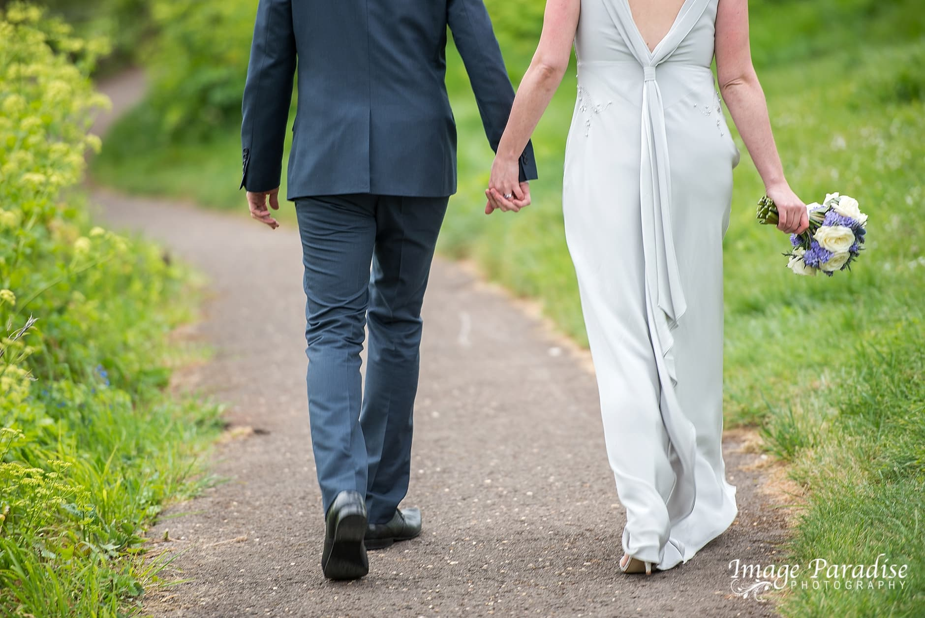 Bride & Groom walking hand in hand by Clifton suspension bridge