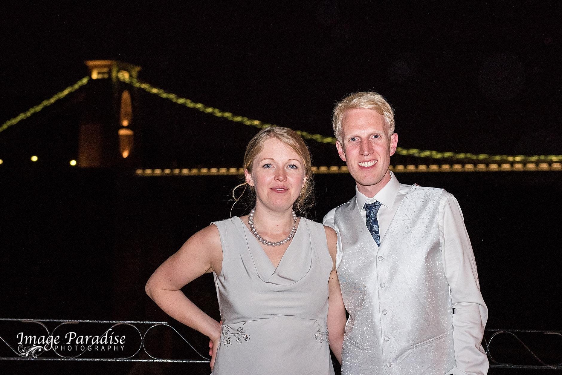 Night image of bride & groom next to the suspension bridge