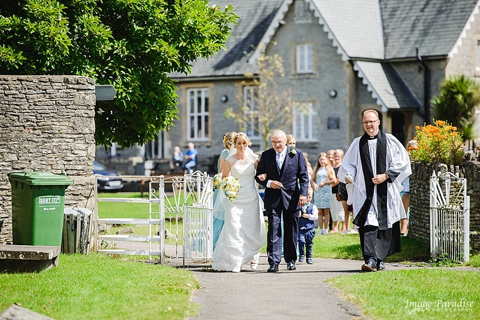 Father walks bride through the garden of St Michaels church Bristol