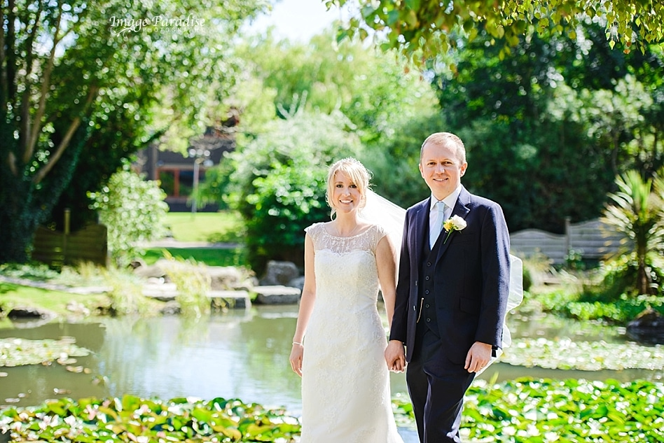 Bride & groom stood near the pond of the Aztec west hotel
