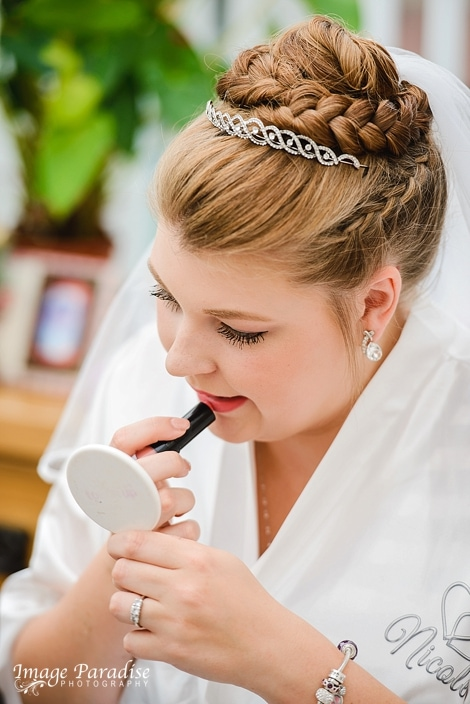 Bride applying lipstick for a wedding at Mercure Bristol North