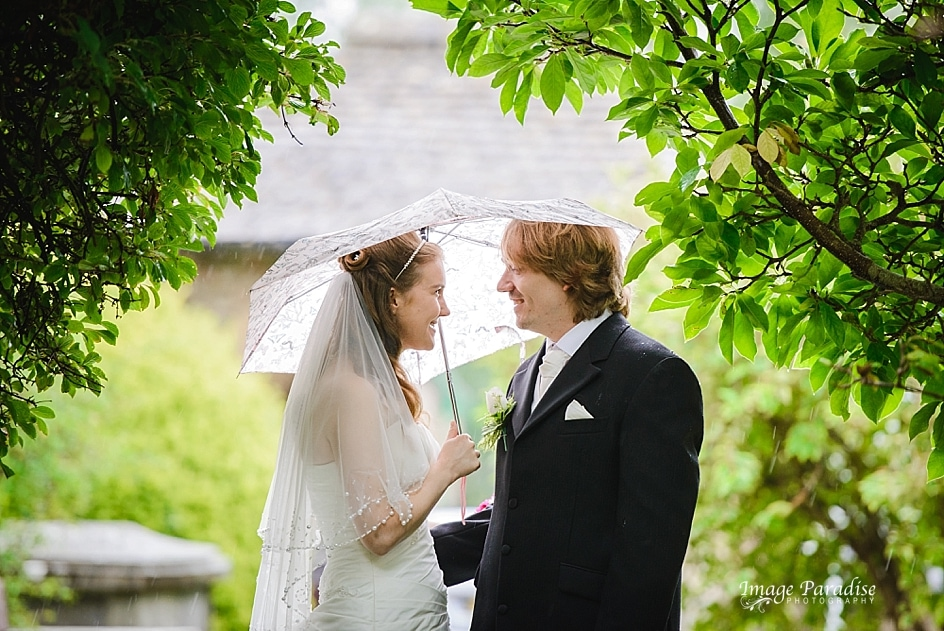 Bride & groom on their wedding day in the rain outside St Mary's Church in Yate