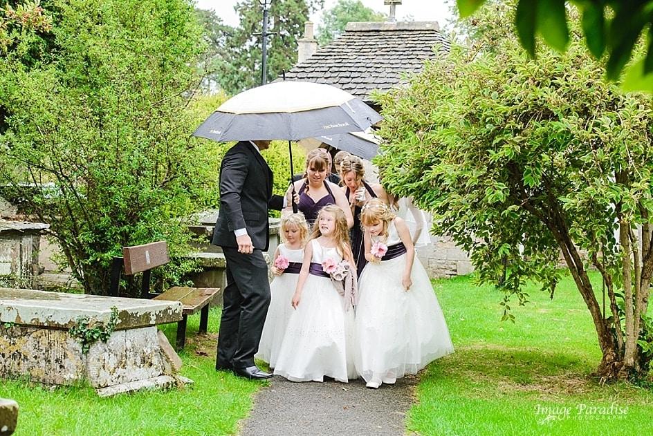 Bridesmaids walking through church garden
