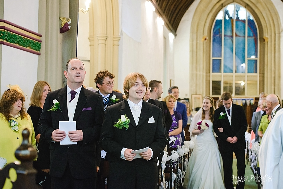Bride walking down the aisle of St Mary's church in Yate