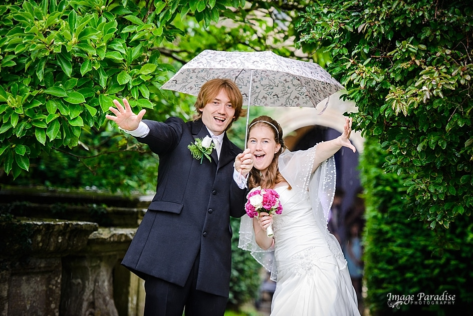 Bride & groom under umbrella at St Mary's church Yate