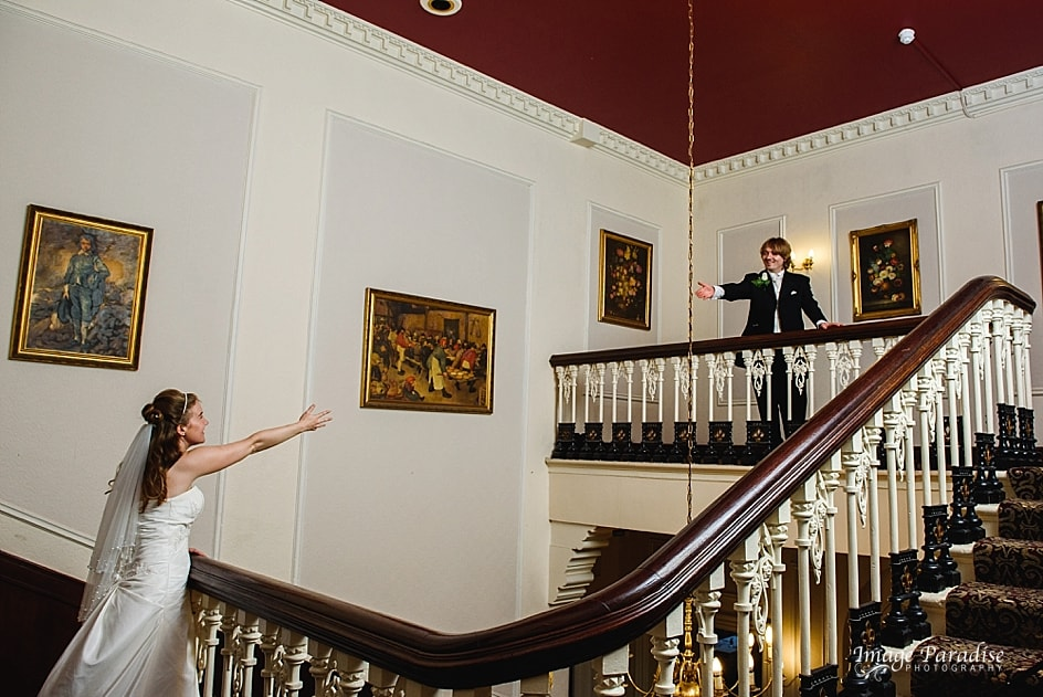 fun picture of bride & groom on the stairs of Stanshawes