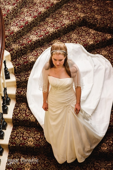 Bride walking down the stairs at Stanshawes
