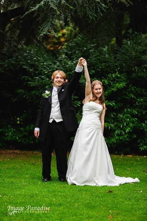 bride & groom having fun in the garden of Stanshawes