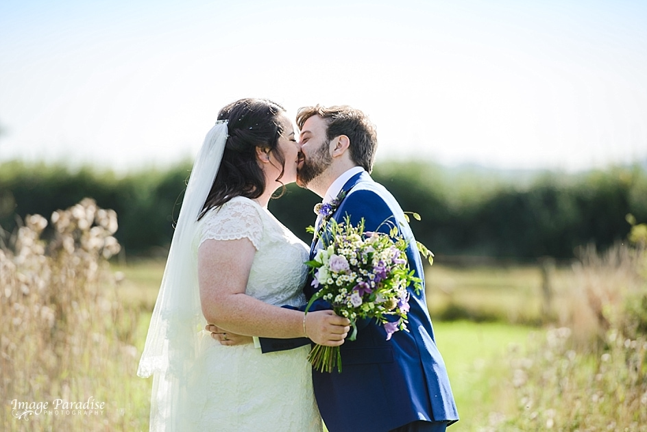 Newly married couple sharing a kiss in the grounds of Hyde Barn