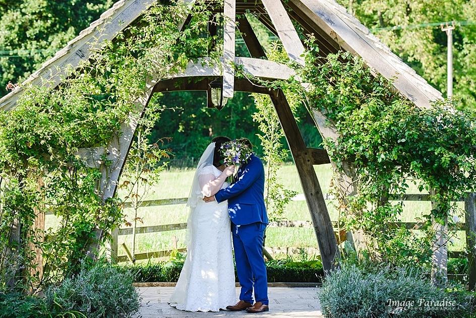 Bride and groom hiding behind flowers