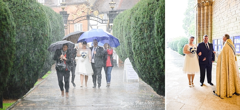 Bride walking in the rain in the grounds of Tewkesbury Abbey