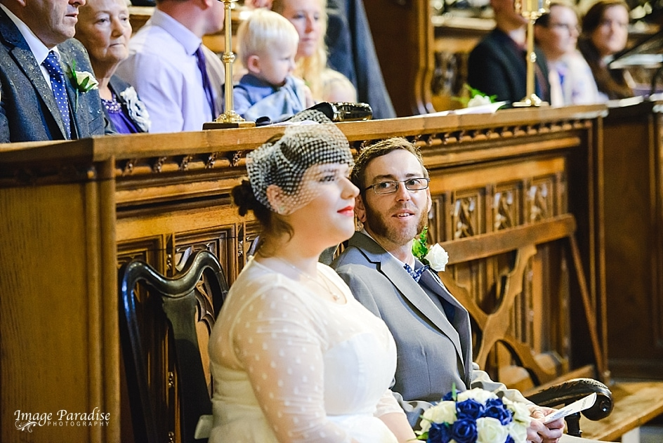 Couple listening to wedding reading at Tewkesbury Abbey