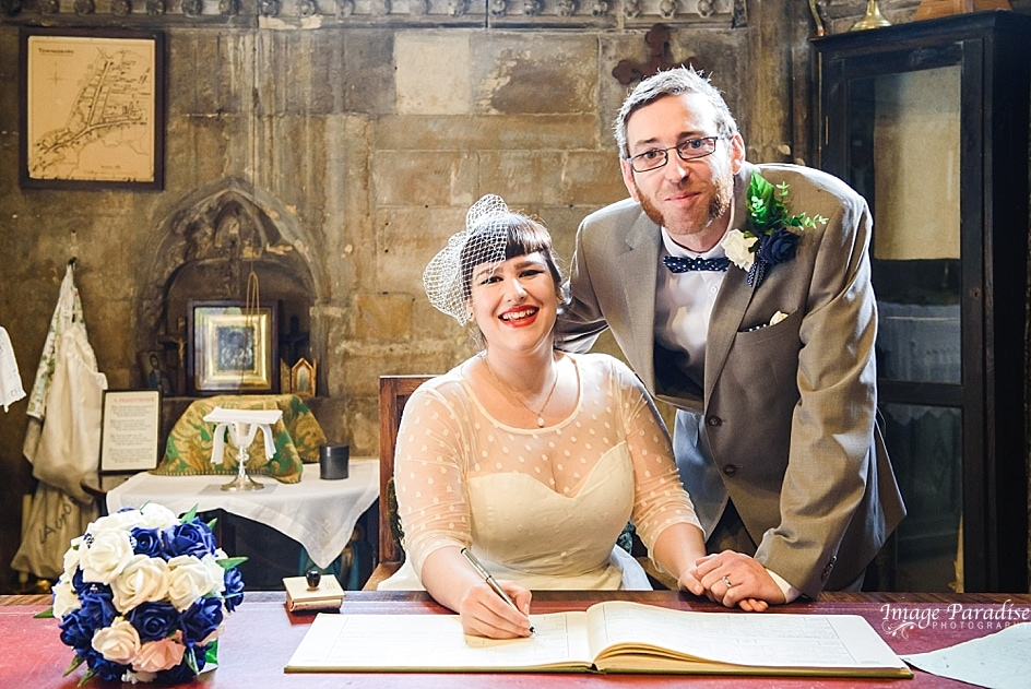 Newly married couple signing marriage register at Tewkesbury Abbey