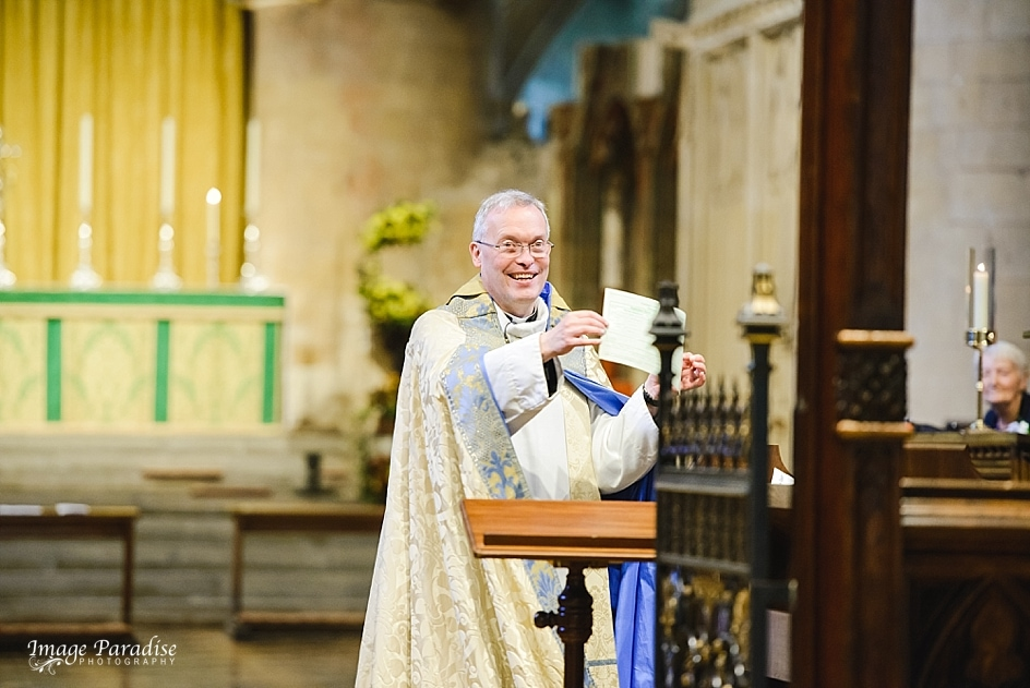 Reverend Paul Williams showing marriage certificate at Tewkesbury Abbey