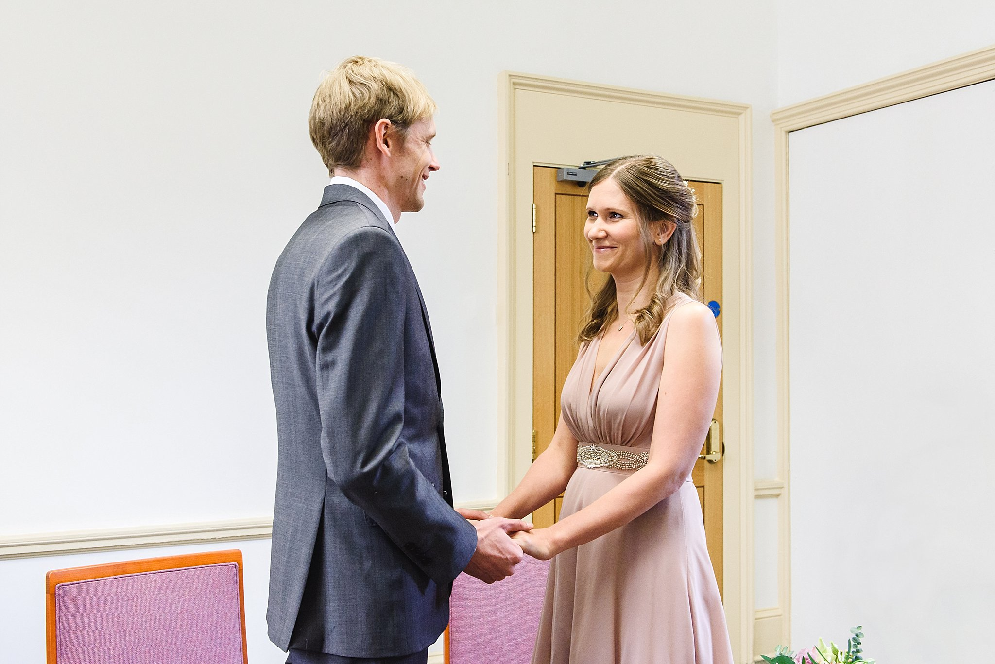 couple holding hands at their Intimate wedding ceremony Statutory rooms Bristol registry office
