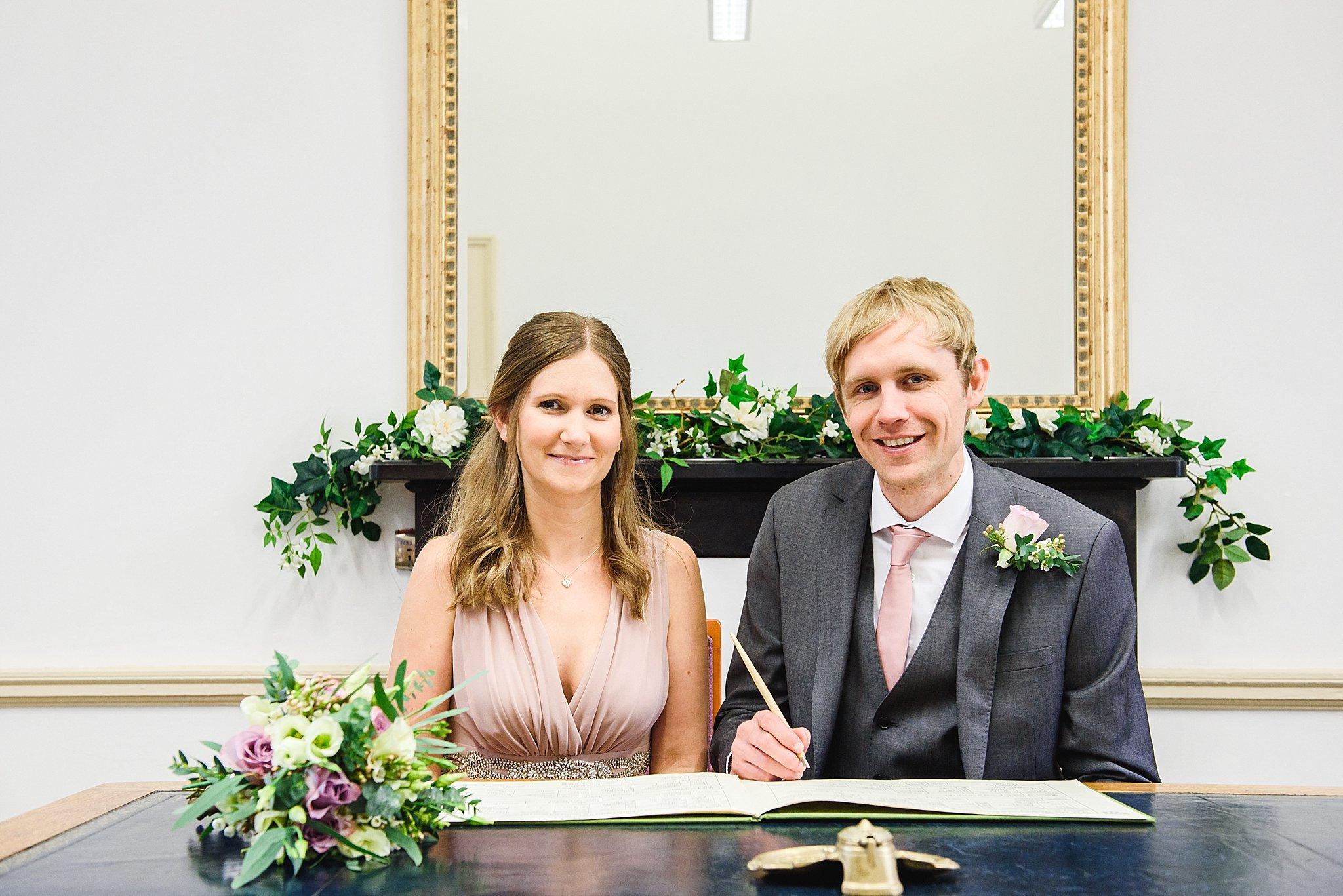 signing the register at intimate Bristol registry office ceremony