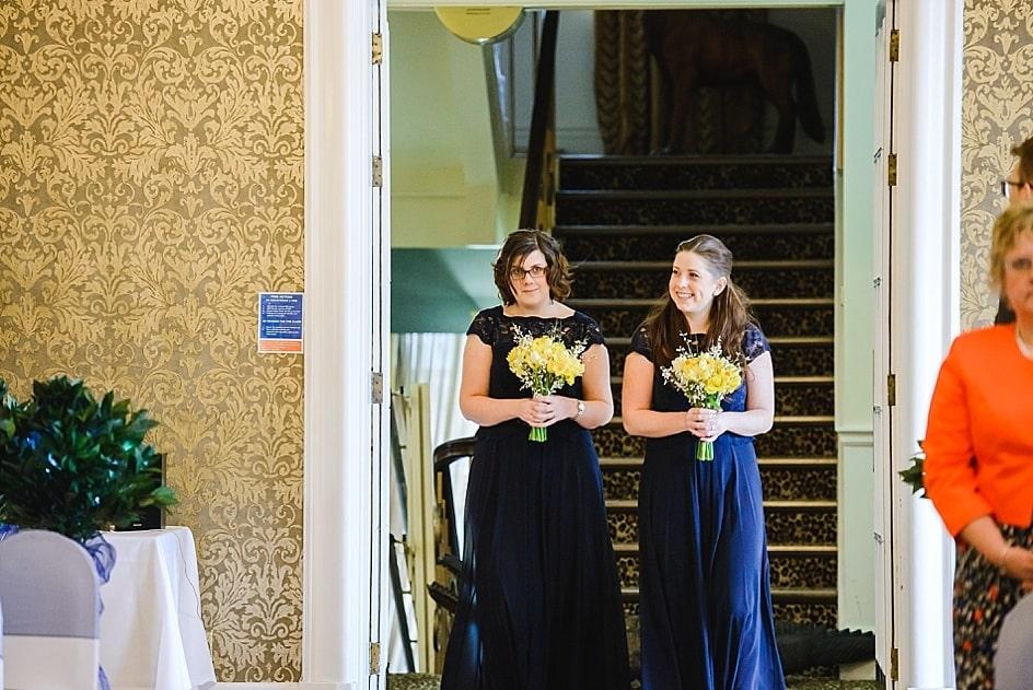 two bridesmaids walking dow the isle of Clifton Pavilion Bristol zoo wedding