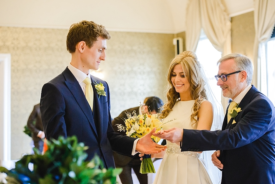 Father of the bride hands over his daughters hand at wedding ceremony at Clifton Pavilion. Bristol zoo wedding