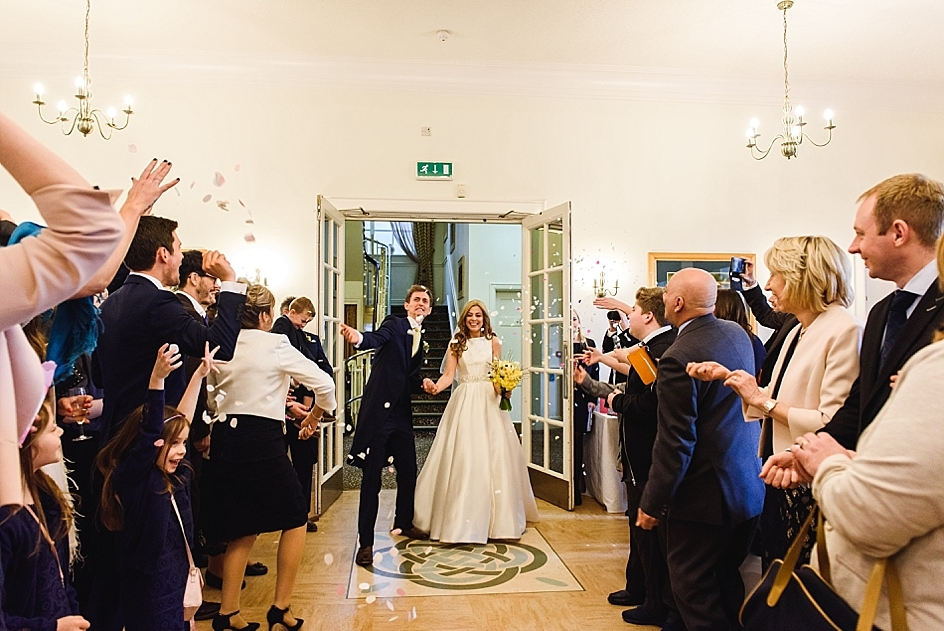 indoor confetti being thrown at a newly married couple at their Bristol zoo wedding