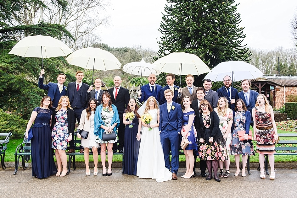 A small wedding group photo in the rain at Bristol zoo wedding. The men hold umbrellas for the ladies