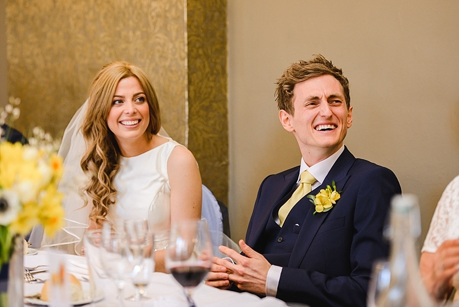 Bride and groom laughing at the best mans speech at their Bristol zoo wedding