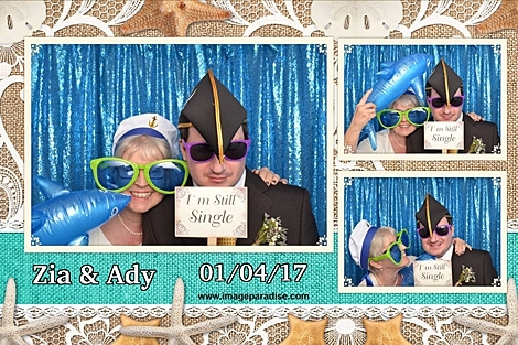 Couple wear sailor hats and sun glasses at this beach themed wedding photo booth