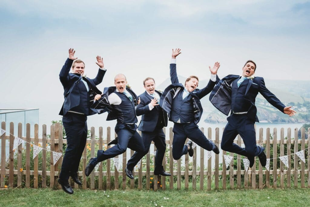Groomsmen jumping with the sea in the background of the garden at Sandy Cove hotel Ilfracombe