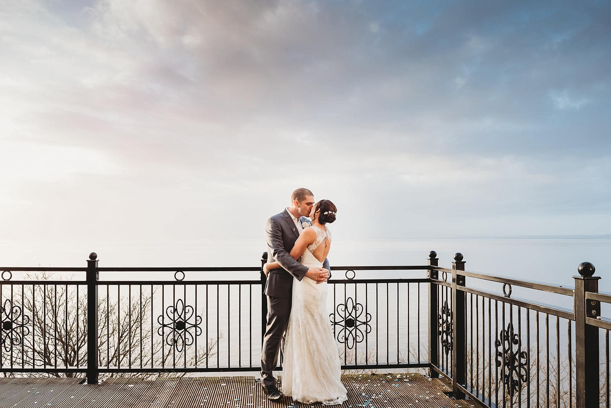 Bride & groom kissing on the balcony of Walton Park hotel over looking the Water at Cleavdon