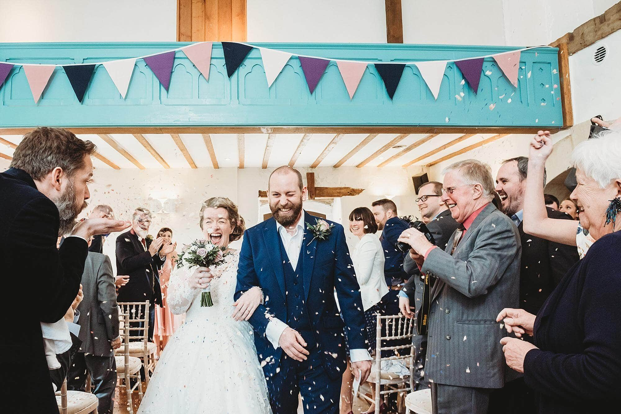 Guests throw confetti over the bride and groom as they walk down the aisle indoor Priston Mill Water mill