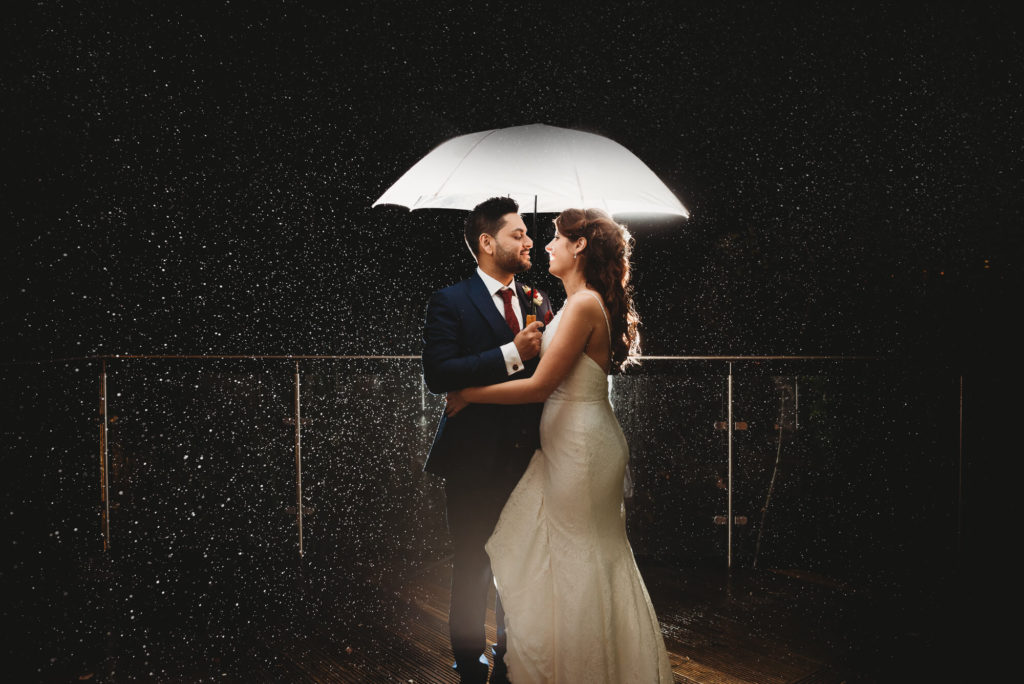 bride and groom holding an umbrella at night in the rain backlit