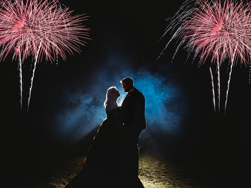 Couple are backlit by Fireworks at the grounds of Old Down Manor estate on their wedding day