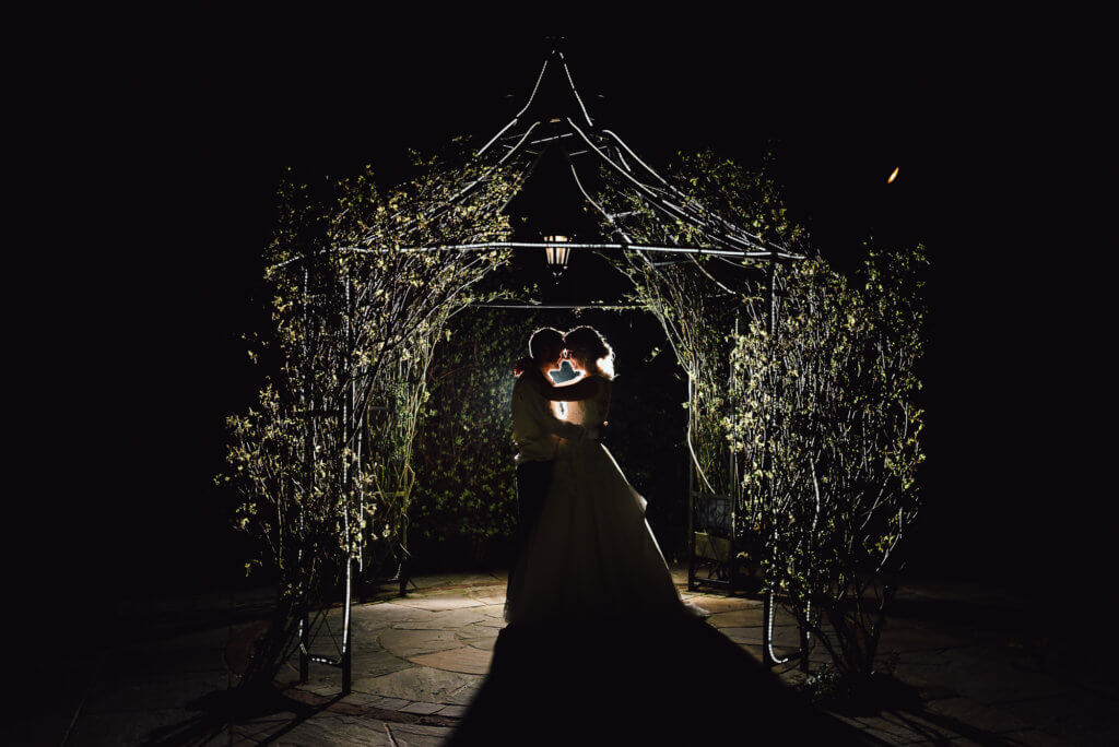 bride and groom hold each other in a tight embrace under a night lit podium