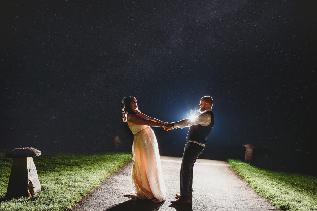 A couple dance on a path at Aldwick Court farm at night backlit with stars