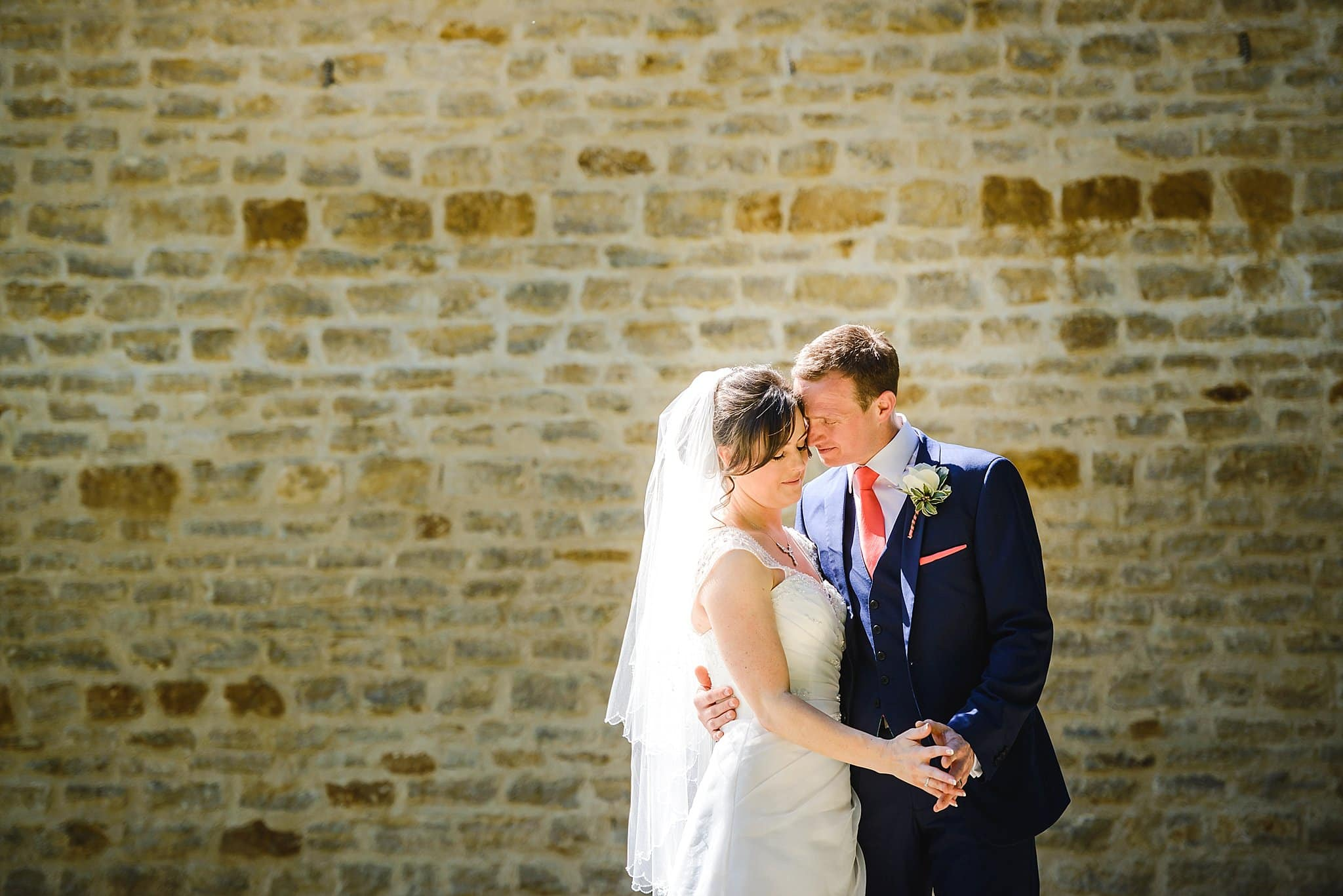 Bride & groom holding hands with a brick backdrop in the grounds of The Hare & Hounds wedding venue Tetbury