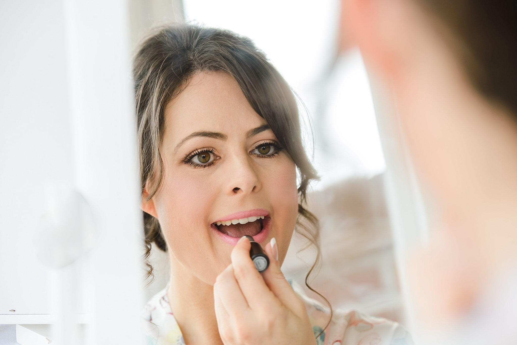 Bride applying lipstick getting ready for her wedding at Hare and Hounds, Tetbury