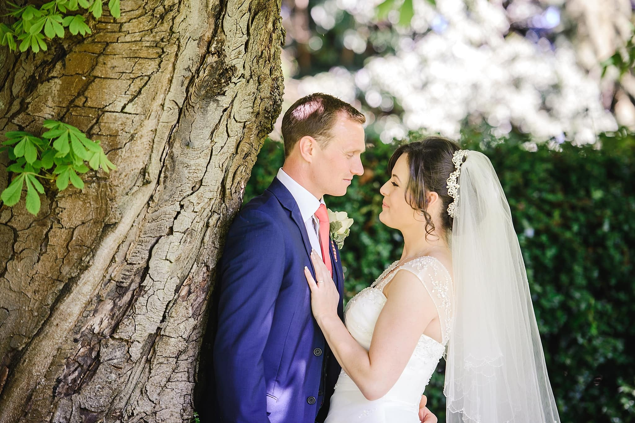 Couple lean against a tree for their wedding photos in the garden of the Hare and Hounds, Gloucestershire