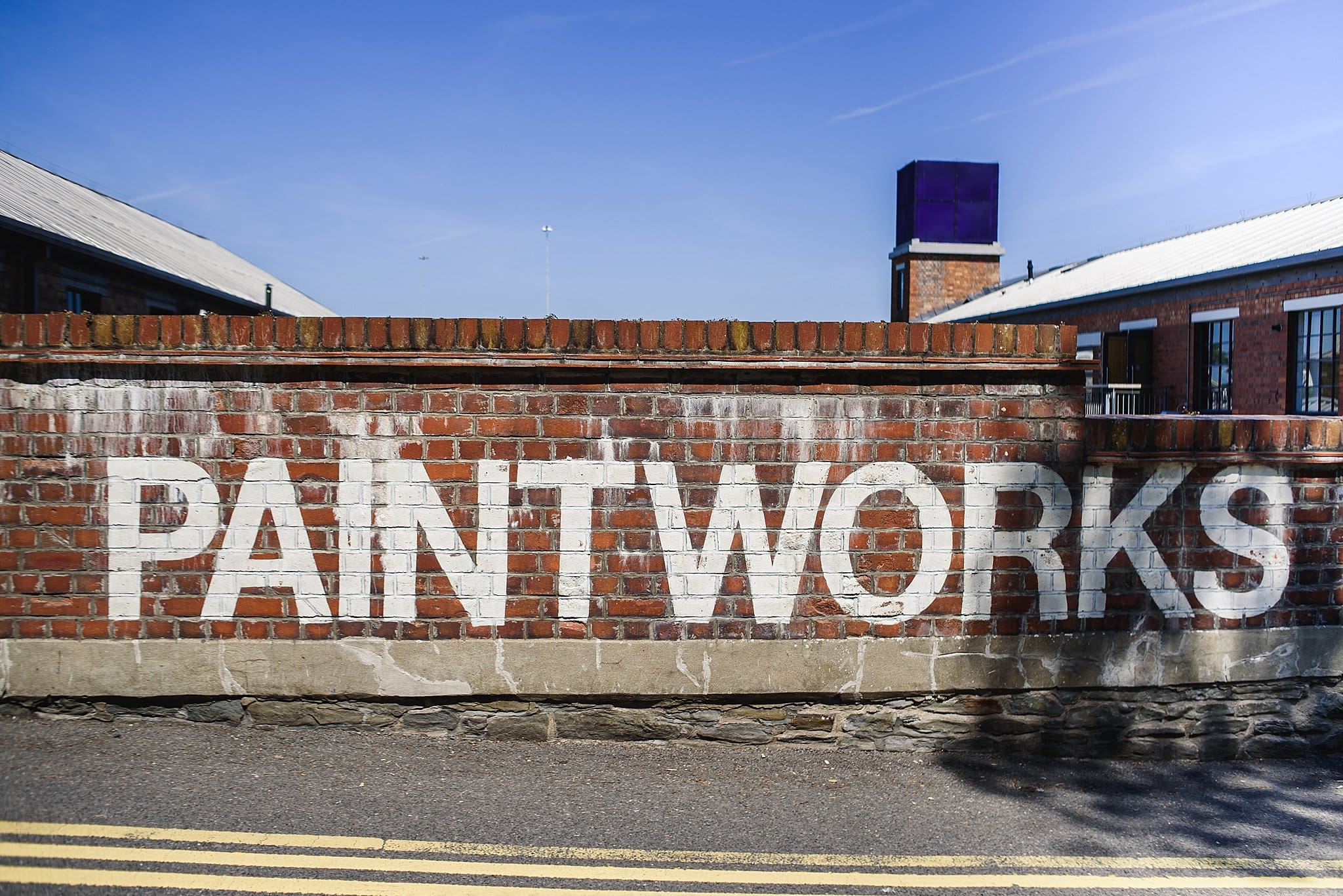 The Paintwork's sign painted on a brick wall