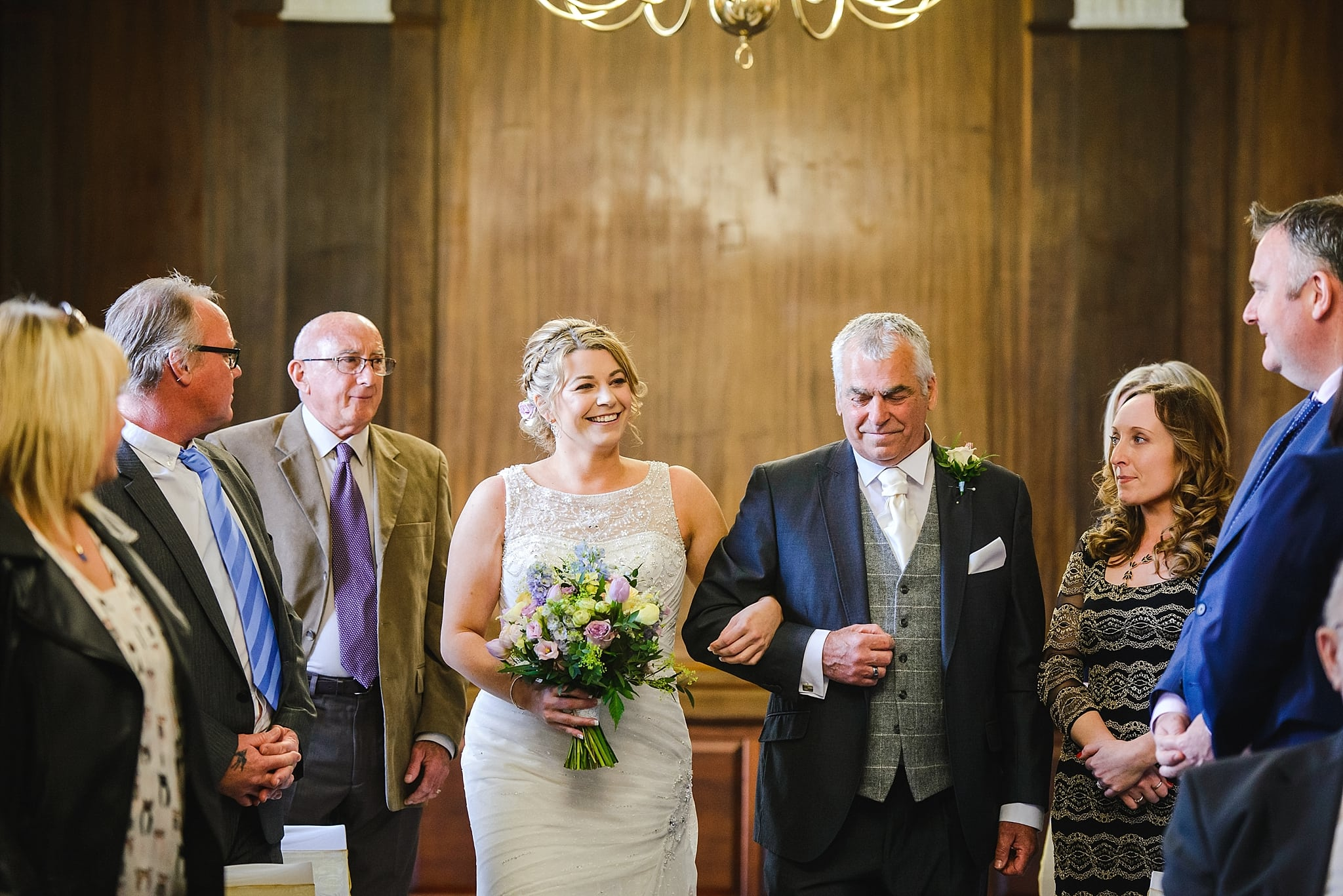 Bride walking arm in arm with her father down the aisle at Trowbridge registry office