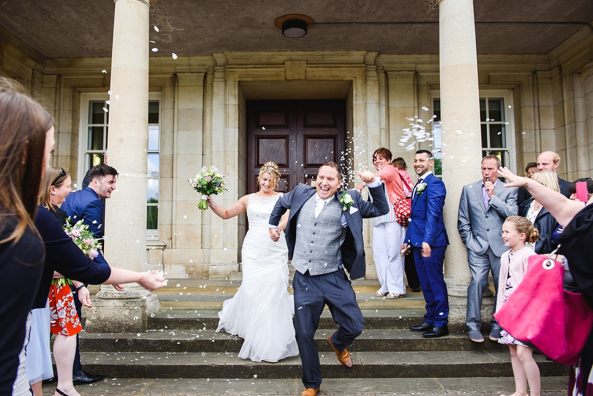 Couple dashing down the steps outside of Trowbridge registry office
