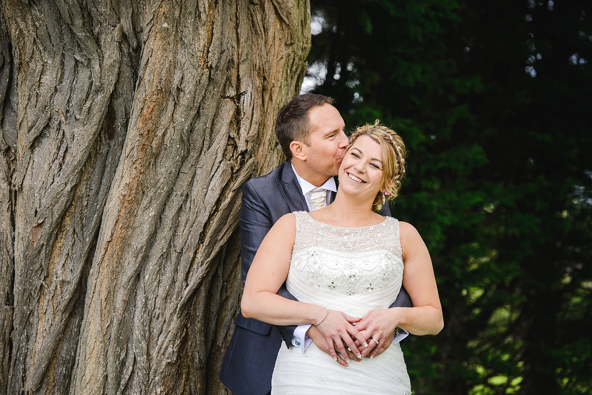 Couple stood near a tree in the garden of Leigh park hotel wedding venue