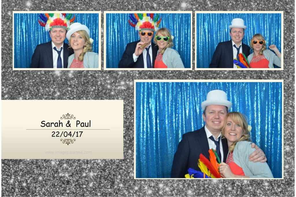 A couple strike a pose in the blue curtain photo booth.