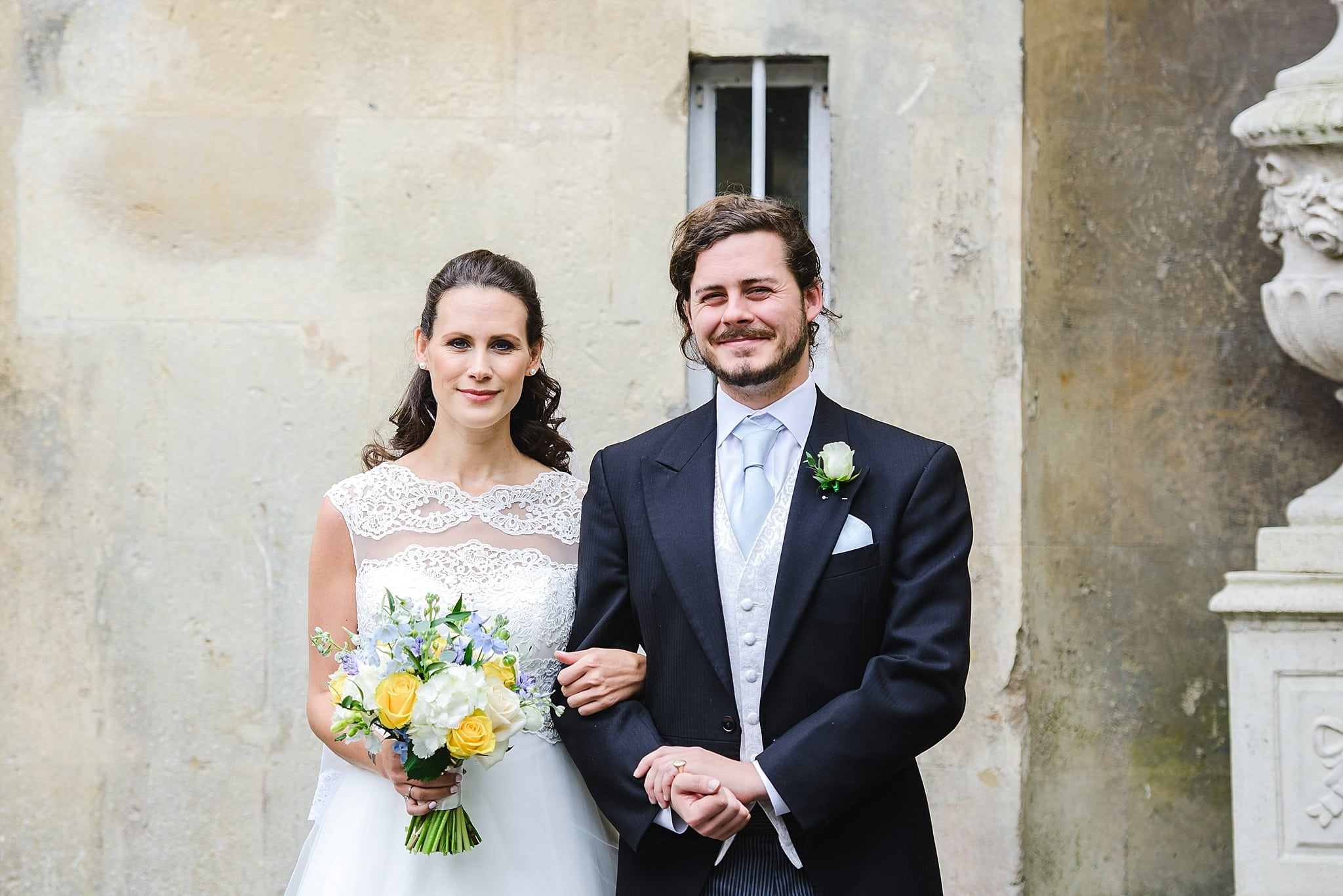Bride and her brother posing for photo's outside Bailbrook House