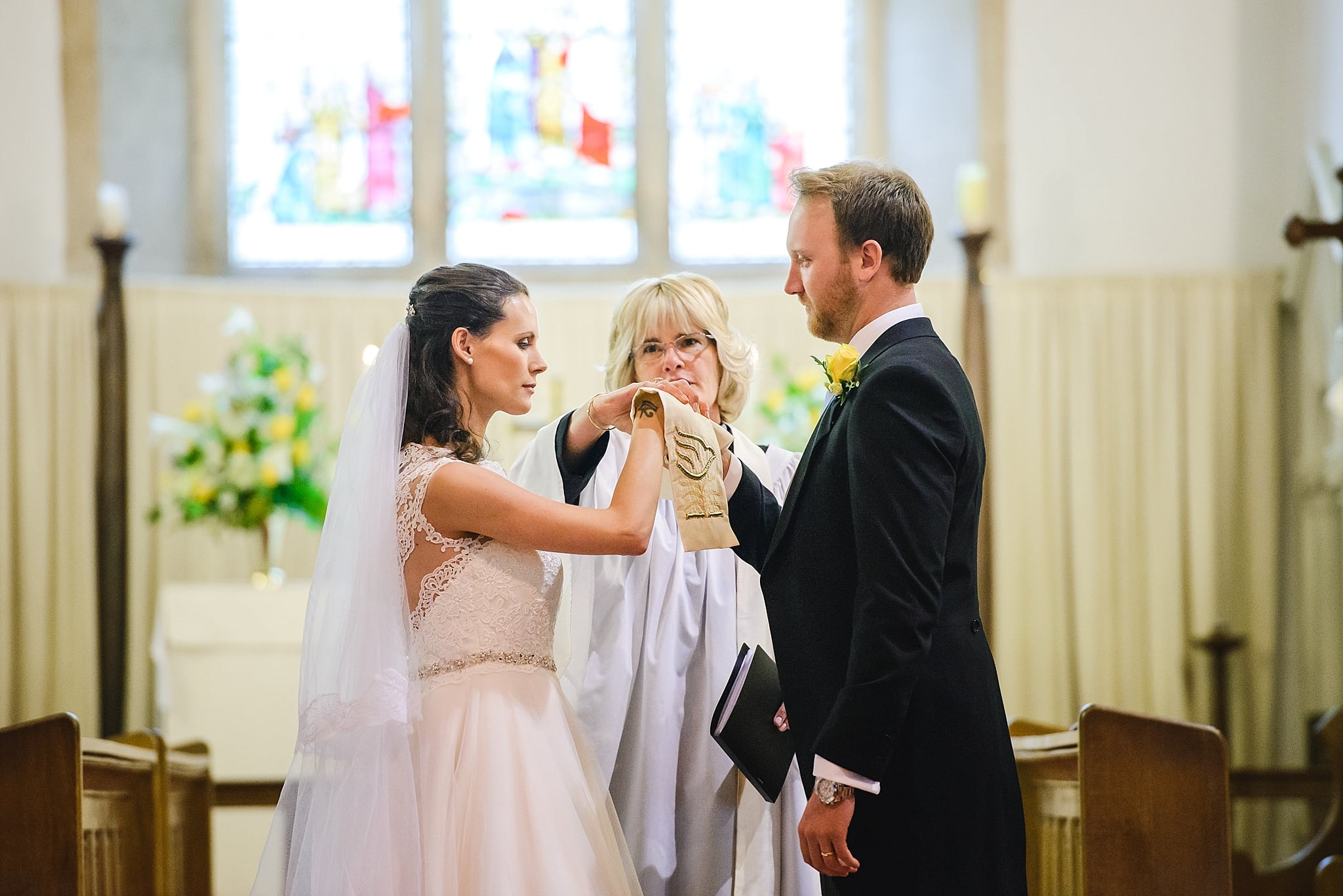Bride and groom have a blessing at St Swithins church, Bathford