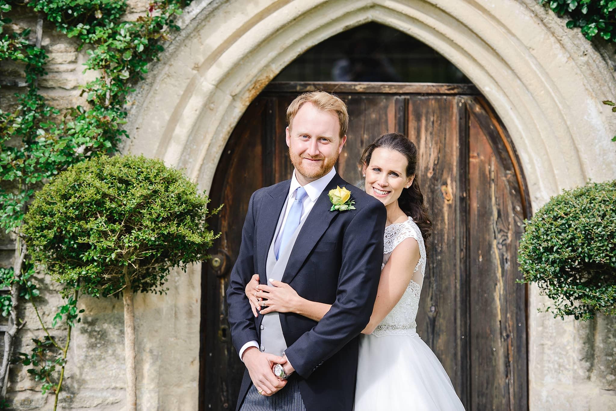 Bride hugs her groom from behind in front of an old door at Wick Farm wedding venue