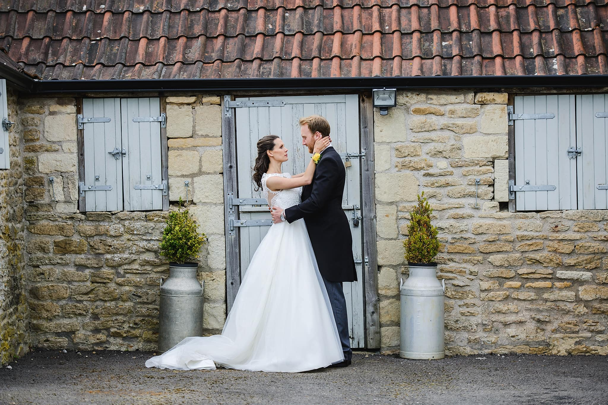 Couple hold each other outside of one of the out houses at Wick Farm