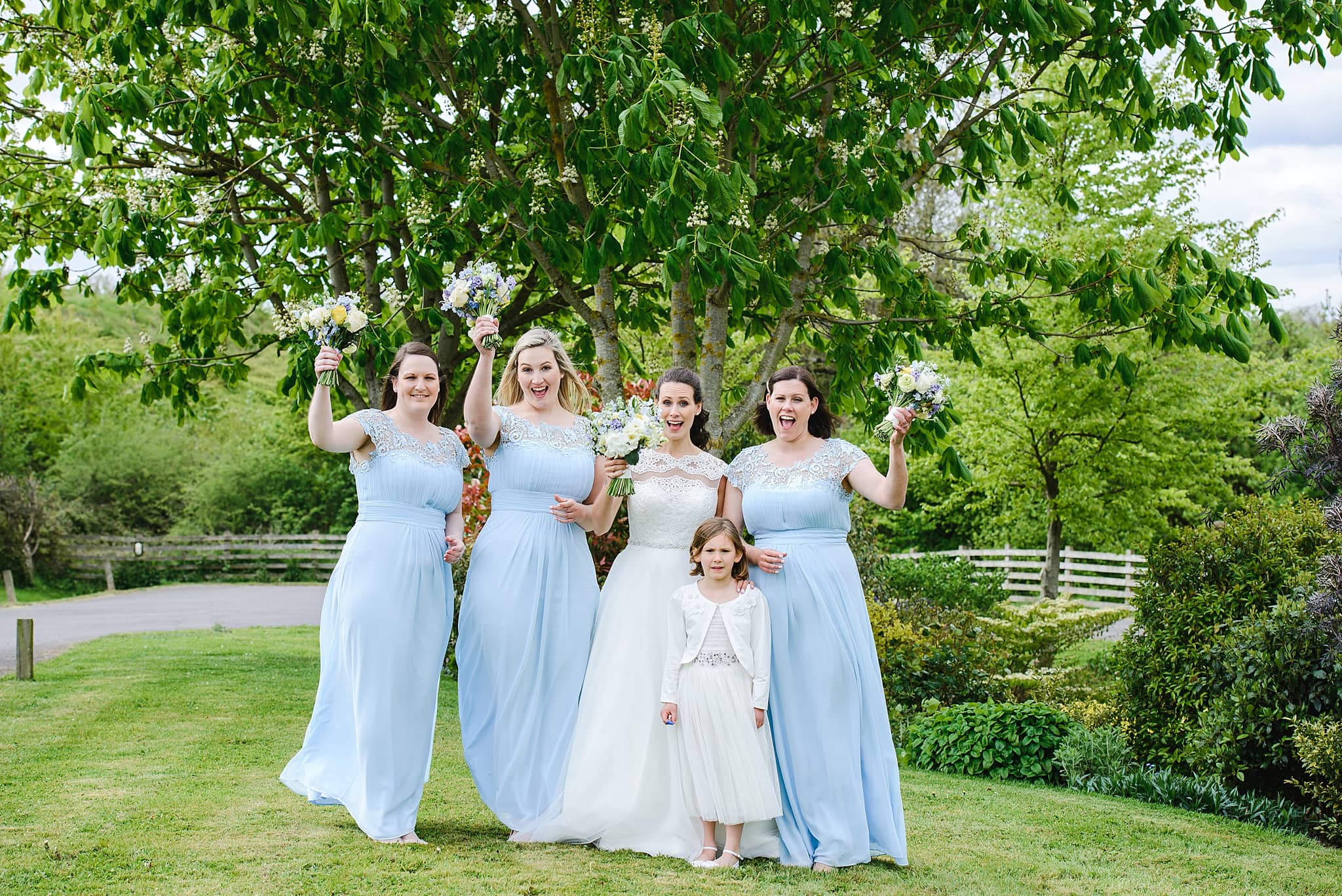 Bridesmaids pose in the garden of Wick Farm wedding venue