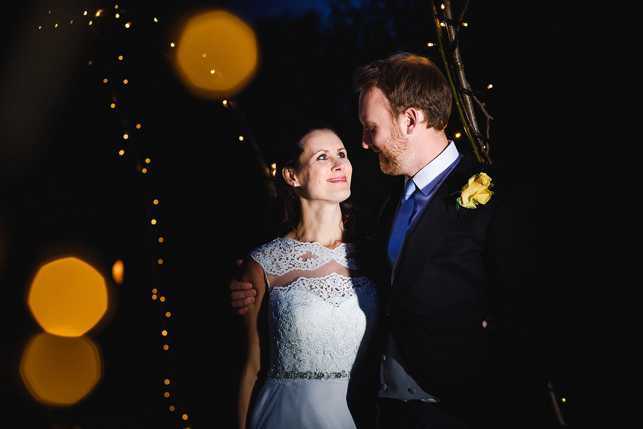 Bride and groom stare at each other at night in the grand of wick farm. Lit artistically with fairy lights