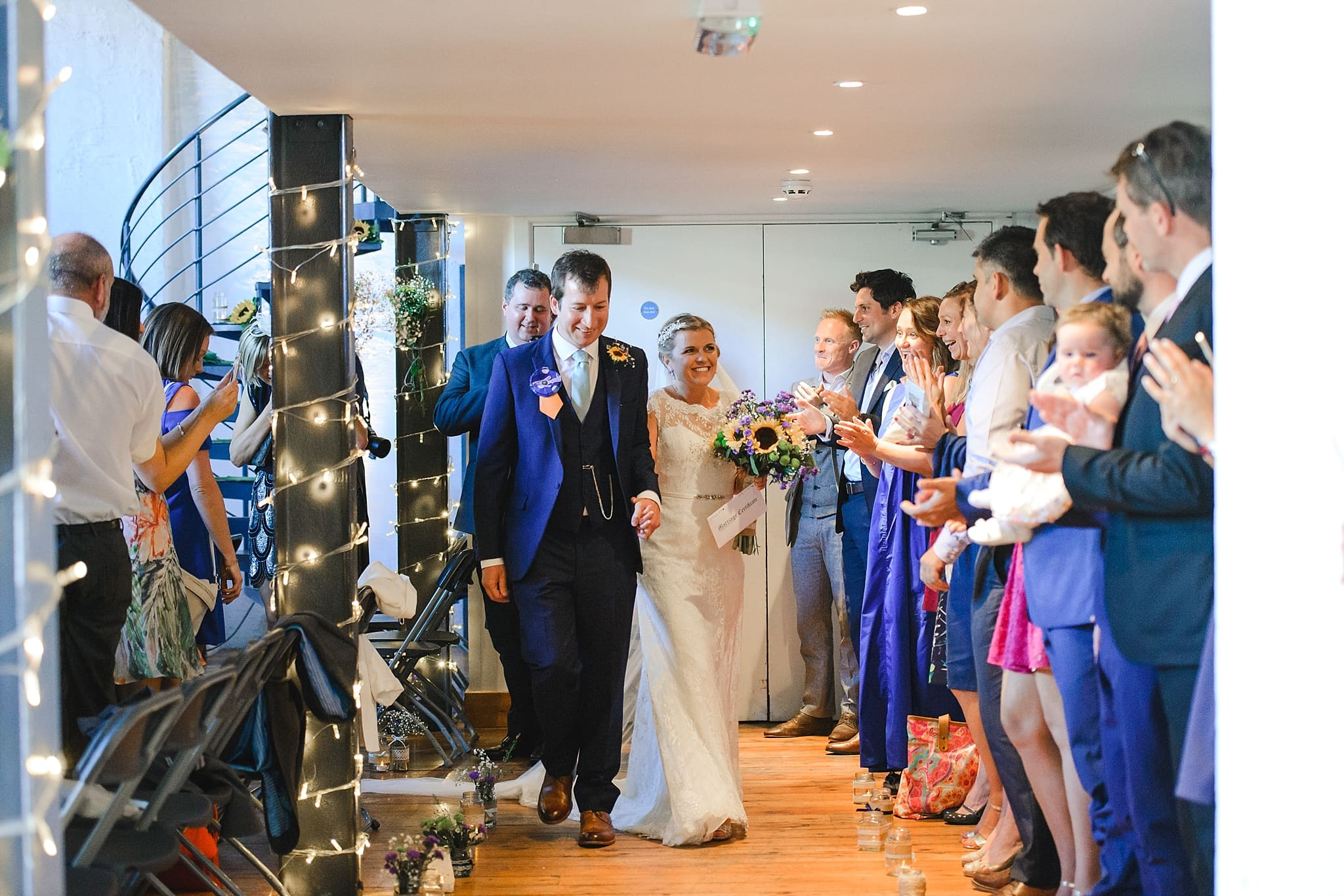 couple walk past their guests at the end of the ceremony at the Paintwork's
