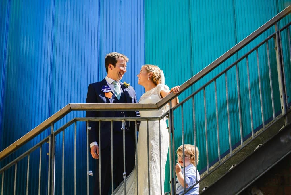 Couple stood on the stairs at the Paintwork's wedding against blue and green backdrop