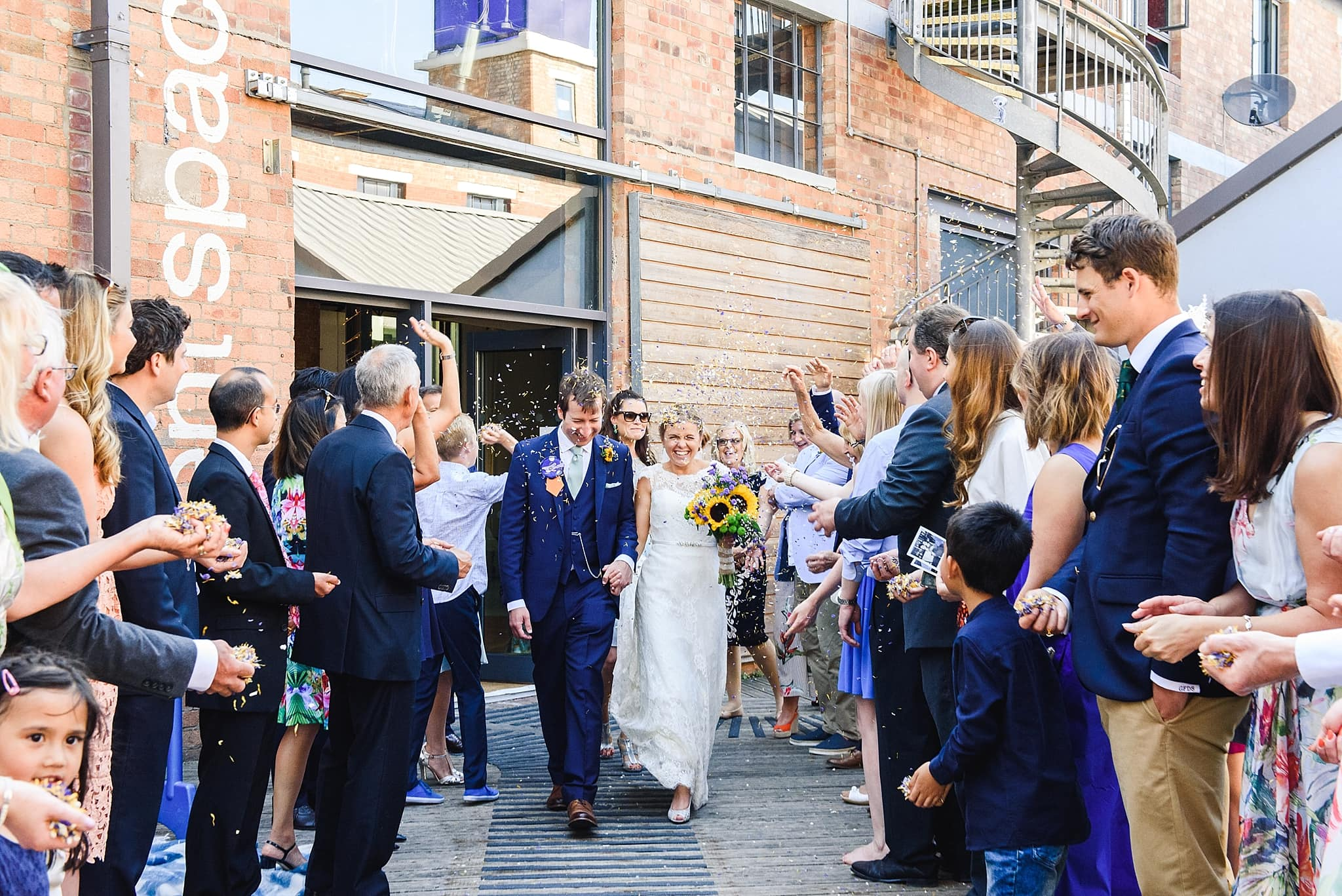 guests throw confetti at newly married couple leaving the Paintwork's event space wedding